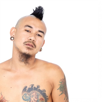 Ritratto del ragazzo punk asiatico arrabbiato e pazzo con stile di capelli, piercing e tatuaggio del mohawk isolati su una parete bianca