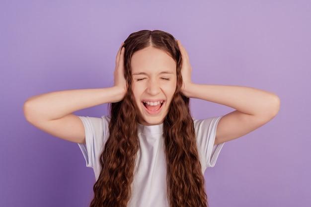 Ritratto di una donna arrabbiata esausta con le mani che copre le orecchie urlando evita il rumore su sfondo viola