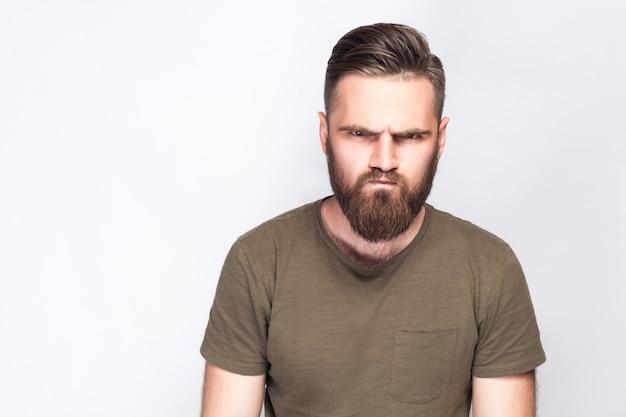 Ritratto di uomo barbuto triste arrabbiato con maglietta verde scuro su sfondo grigio chiaro. girato in studio. .