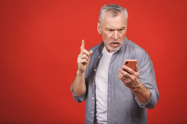 Ritratto dell'uomo senior arrabbiato che parla sul telefono cellulare isolato sulla parete rossa della parete. emozioni negative.