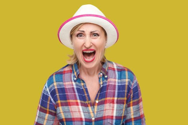 Ritratto di donna matura elegante moderna arrabbiata o scioccata in stile casual con cappello bianco in piedi e guardando la macchina fotografica e urlando. studio al coperto colpo isolato su sfondo giallo.