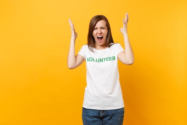 Ritratto arrabbiato scioccato urla giovane donna in t-shirt bianca con scritta iscrizione verde titolo volontario isolato su sfondo giallo. aiuto volontario di assistenza gratuita, concetto di lavoro di grazia di carità.