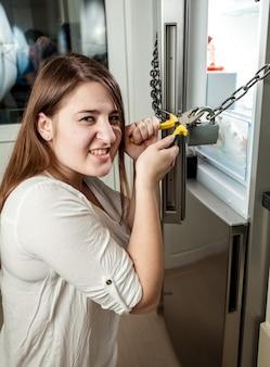 Ritratto di donna arrabbiata che taglia catena sul frigorifero con frese