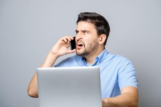 Ritratto del giovane arrabbiato che grida sul suo telefono cellulare