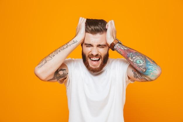 Ritratto di un giovane arrabbiato che indossa abiti casual in piedi isolato sopra il muro giallo, urlando, soffre di mal di testa
