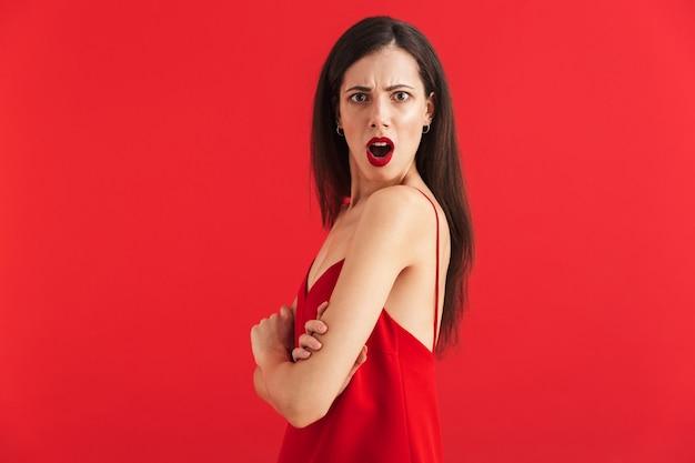 Ritratto di una giovane donna arrabbiata in abito isolato, tenendosi per mano