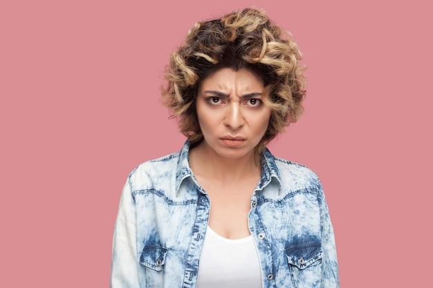Ritratto di giovane donna arrabbiata con l'acconciatura riccia in camicia blu casual in piedi e che guarda l'obbiettivo con viso temperamento aggressivo. girato in studio al coperto, isolato su sfondo rosa.