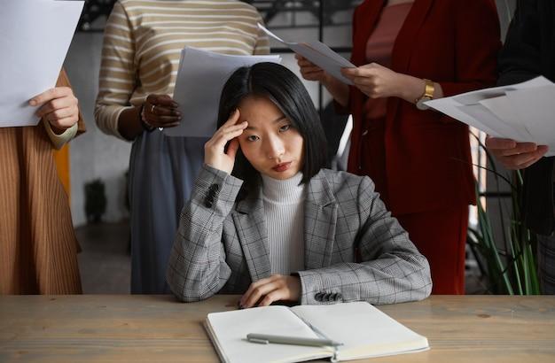 Ritratto di una donna d'affari asiatica infastidita che guarda la telecamera circondata da un gruppo di persone, concetto di stress, spazio copia