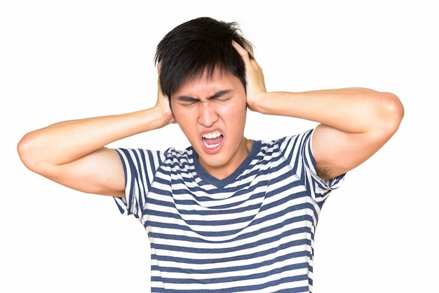 Ritratto di uomo asiatico infastidito che copre le sue orecchie isolato contro il muro bianco