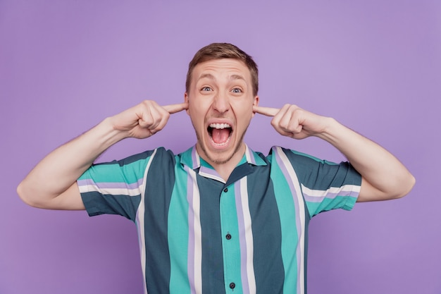 Ritratto di un ragazzo irritato e infastidito, le dita chiudono le orecchie aprono la bocca gridano forte su sfondo viola