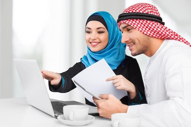 Ritratto di coppia araba con laptop su sfondo