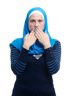 Ritratto della femmina musulmana araba che copre la sua bocca isolata su backgound bianco