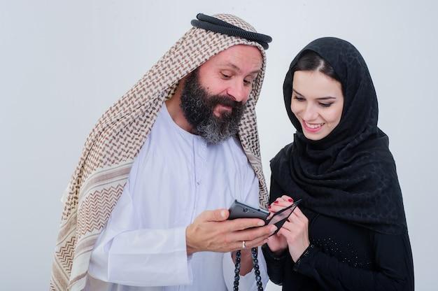 Ritratto di coppia vestita in modo arabo gioca con il telefono cellulare.