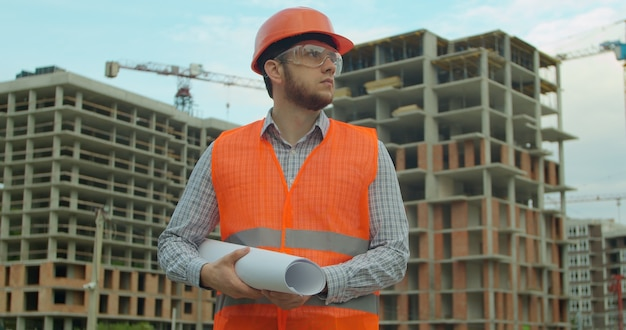 Ritratto di un architetto o un costruttore in elmetto in piedi davanti all'edificio in costruzione.