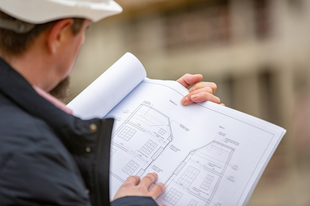 Ritratto di architetto al lavoro con casco in un cantiere edile, legge il piano, progetti di carta