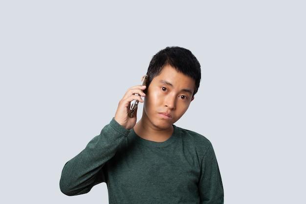 Ritratto di asia uomo parlando smartphone isolato su sfondo grigio.
