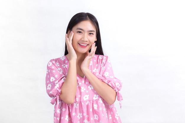Ritratto bella ragazza asiatica in abito rosa e capelli lunghi neri. le sue mani toccano la guancia, sorridono, mostrano una bella pelle su sfondo bianco.