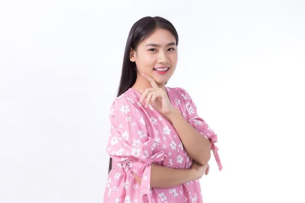 Ritratto bella ragazza asiatica in abito rosa e capelli lunghi neri le sue mani toccano il sorriso sulla guancia