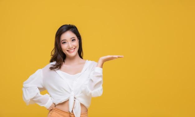 Sorridere asiatico bello felice della giovane donna del ritratto allegro e che esamina macchina fotografica isolata sul fondo giallo dello studio