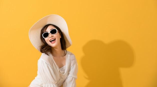 Bella giovane donna felice asiatica del ritratto con sorridere degli occhiali da sole e del cappello allegro di estate e esaminando macchina fotografica isolata sul fondo giallo dello studio.