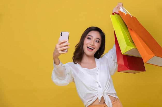 Ritratto asiatico bella giovane donna felice con occhiali da sole sorridente allegro e lei tiene in mano smart phone per selfie e shopping online con borse della spesa su sfondo giallo.
