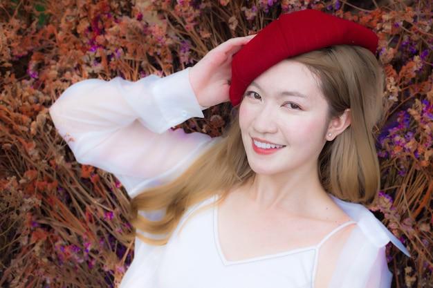 Ritratto di una bella signora asiatica che indossa un abito bianco e un berretto rosso sorride in fiori secchi colorati
