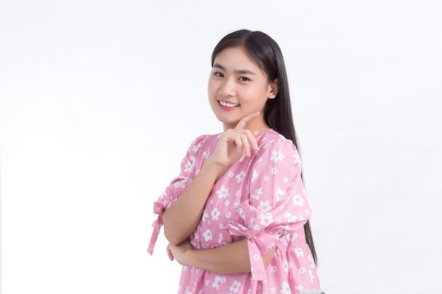 Ritratto bella donna asiatica in abito rosa e capelli lunghi neri le sue mani toccano il sorriso sulla guancia