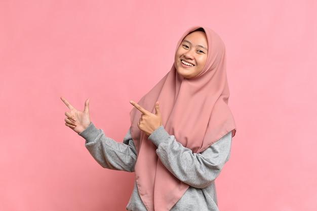 Ritratto di una bella giovane donna musulmana asiatica che punta entrambe le mani con il dito sul lato superiore con una faccia sorridente, isolata su sfondo rosa