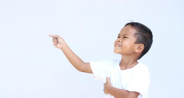 Ritratto di ragazzo asiatico che punta a qualcosa. con copia spazio per la presentazione del prodotto, pubblicità e altro