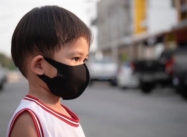 Ritratto della maschera asiatica di usura del ragazzo che prova a proteggere dall'epidemia di coronavirus.