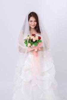 Ritratto della sposa asiatica che indossa l'abito bianco sul bianco.