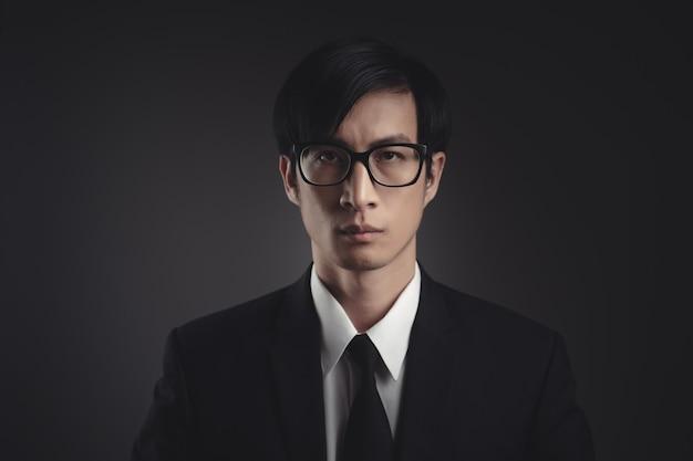 Ritratto di uomo d'affari asiatico in abito nero su fondo nero