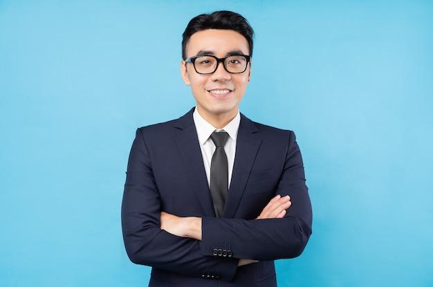 Ritratto di uomo d'affari asiatico con le braccia incrociate e sorridente su una parete blu