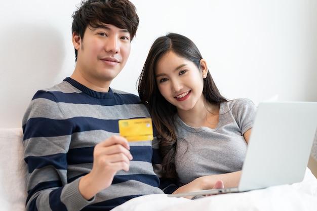 Ritratto di una coppia allegra asiatica che fa shopping online su internet con un computer portatile mentre è seduto sul letto a casa, uomo in possesso di carta di credito con sentirsi felice per il pagamento di un regalo a sua moglie