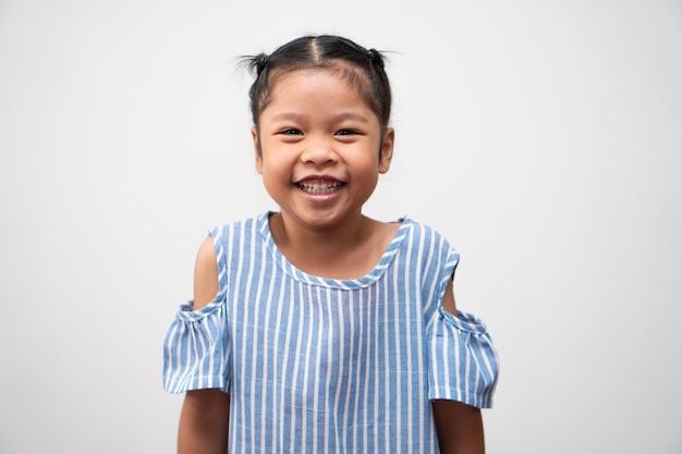 Ritratto di bambino asiatico di 5 anni e per raccogliere i capelli e un grande sorriso su sfondo bianco isolato
