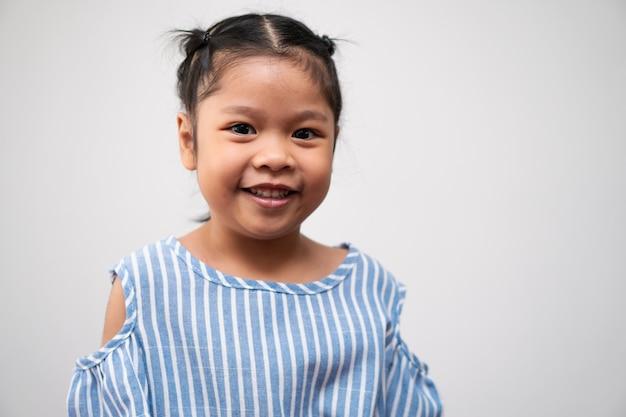 Ritratto di bambino asiatico di 5 anni e per raccogliere i capelli e un grande sorriso