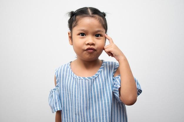 Ritratto di bambino asiatico di 5 anni e per raccogliere i capelli e mettere il dito indice sulla testa e fare il pensiero in posa