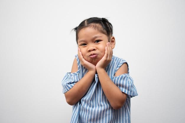 Ritratto di bambino asiatico e per raccogliere i capelli e mettere qui le mani sulle guance e posa divertente