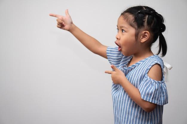 Ritratto di bambino asiatico e raccogliere i capelli e mettere il dito indice in aria e fare la posa eccitata di pensiero