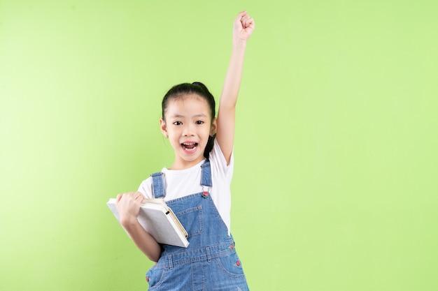Ritratto di bambino asiatico che tiene libro su sfondo verde green