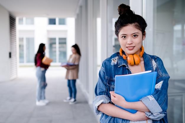 Ritratto di uno studente di college asiatico che tiene le cartelle