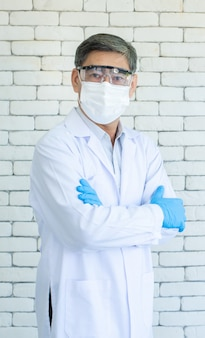 Ritratto di medico o ricercatore anziano asiatico indossare camice da laboratorio, occhiali trasparenti e maschera per il viso in piedi e braccio incrociato con sfondo di mattoni bianchi.