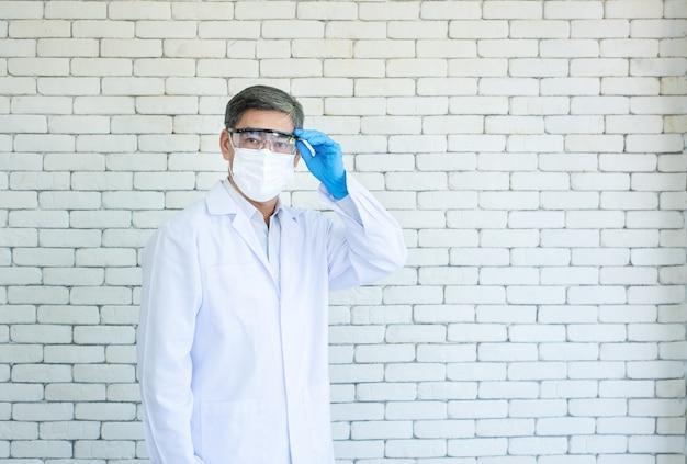 Ritratto di asiatico anziano medico o ricercatore indossare camice da laboratorio e maschera per il viso in piedi e tenere in mano con gli occhiali con sfondo di mattoni bianchi.