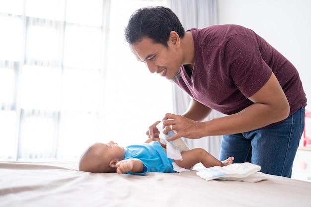 Ritratto del padre asiatico che cambia il suo pannolino del bambino neonato a casa