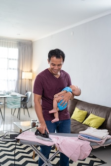 Ritratto del padre asiatico che riveste di ferro i suoi vestiti mentre tiene il suo bambino neonato sulla sua mano