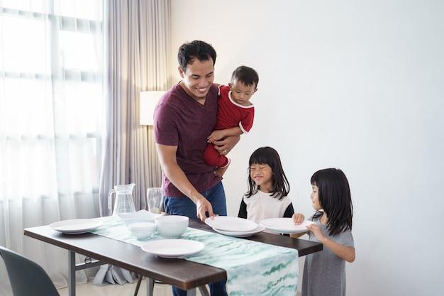 Ritratto del padre asiatico e della piccola figlia che preparano il tavolo da pranzo per la cena