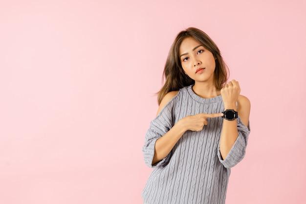 Ritratto di una ragazza asiatica che punta a un orologio da polso è arrabbiata perché i suoi amici sono in ritardo. isolato su uno sfondo rosa