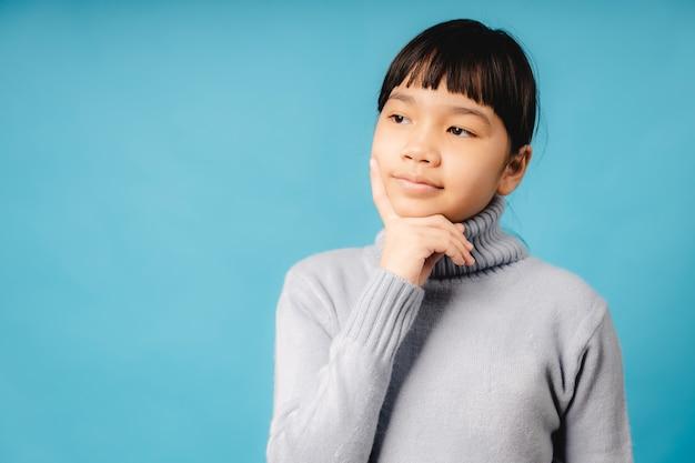 Ritratto di ragazza asiatica che pensa e concetto di idea