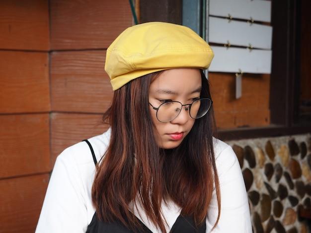 Il ritratto di una ragazza asiatica con occhiali e cappello giallo si siede con la faccia noiosa e stressata durante il viaggio