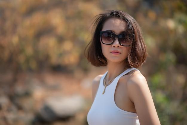 Ritratto di ragazza asiatica con occhiali da sole guarda la fotocamera.